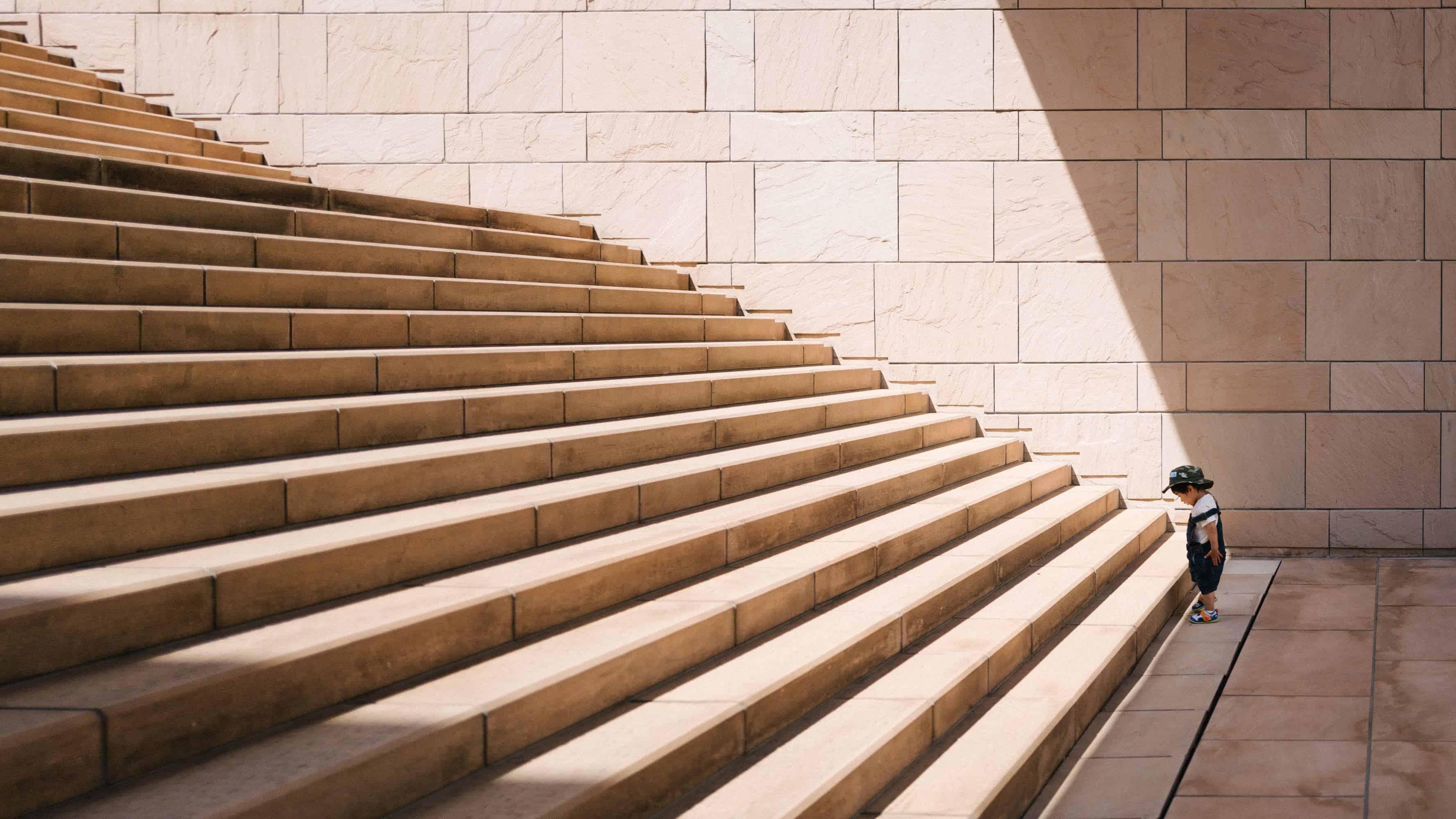 Ein kleiner Junge steht am Fuß einer großen Treppe