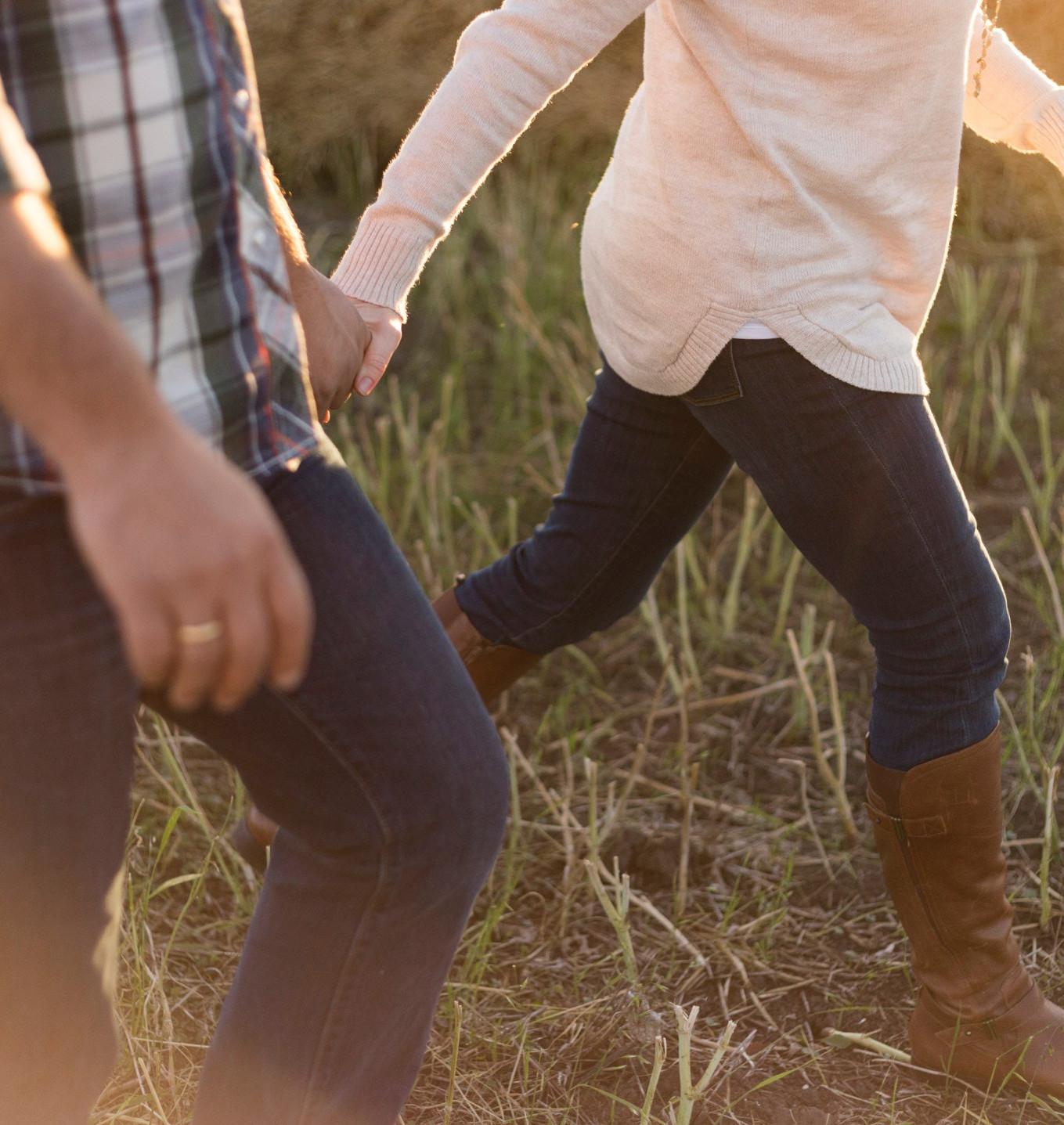 Nahaufnahme eines Paares, das Hand in Hand durch ein Feld läuft